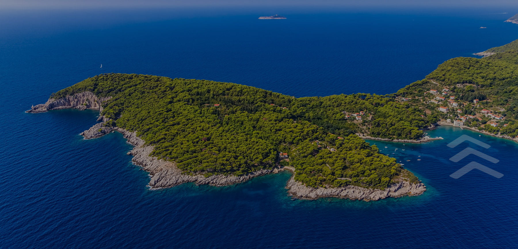 A photo of Kolocep Island, one of the Elaphiti Islands off the coast of DUbrovnik. An arrow is pointing at the location where the hotel is located.